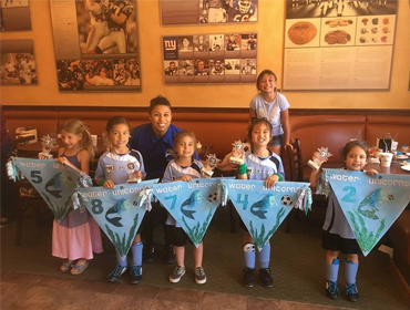 Five little girls wearing light blue soccer uniforms each holding a sign with their jersey numbers at our Huntington Beach restaurant