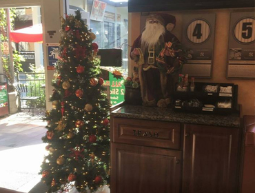 Santa Claus standing next to X-mass tree at our Huntington Beach restaurant