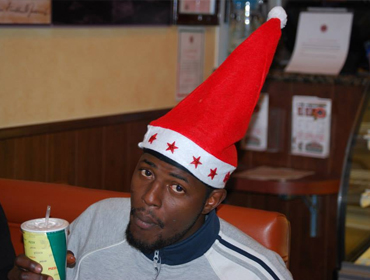 A customer wearning a x-mass cap, holding soft drink in his hand.