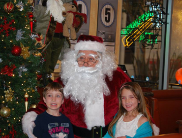 kids smiling and posing to take picture with Santa Claus and x-mass tree at our Huntington Beach restaurant