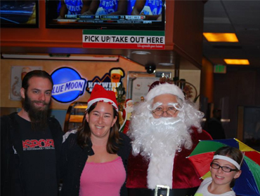 A happy family posing for picture with Santa Claus at our Huntington Beach restaurant