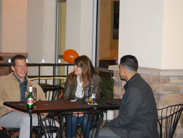 three individuals seating and conversating at our Huntington Beach restaurant