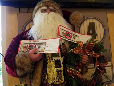 Santa Claus holding gift certificate with intention to hand them out to customers at our Huntington Beach restaurant