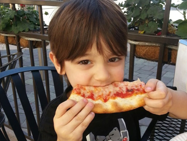 Kid eating slice of our pizza outside of our Huntington Beach restaurant