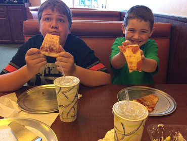 Kids are enjoying eating their pizza