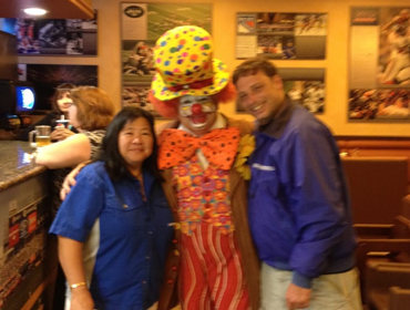 Two of our staff (Male and Female) taking picture with a clown at our Huntington Beach restaurant