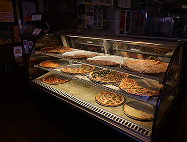 Different large size pizzas displayed inside of our front counter cooler.