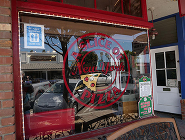 Our A Slice of New York Pizza logo sign on glass wall at our Seal Beach restaurant